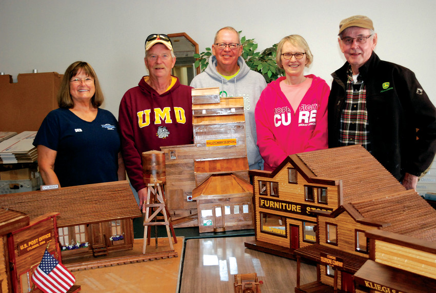 CYLINDER ON DISPLAY -- Cylinder from days gone by is being replicated one building at a time by Joe Joyce of Emmetsburg. The ten buildings that have been completed are on display at the Cylinder Post Office. Pictured (from the left) are Deb Weisbrod, Greg Sween, Mayor Harry Bormann, City Clerk Kathy Heng, and Joe Joyce.          --Jane Whitmore photos