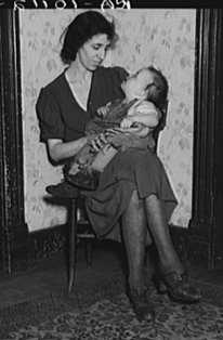 Wife of Homer Sharer and the baby, one of five children. Former tenant farmers and hired hands. They are now living on unemployment relief in Estherville, Iowa - Photograph by Lee Russell, part of the Farm Security Administration Collection