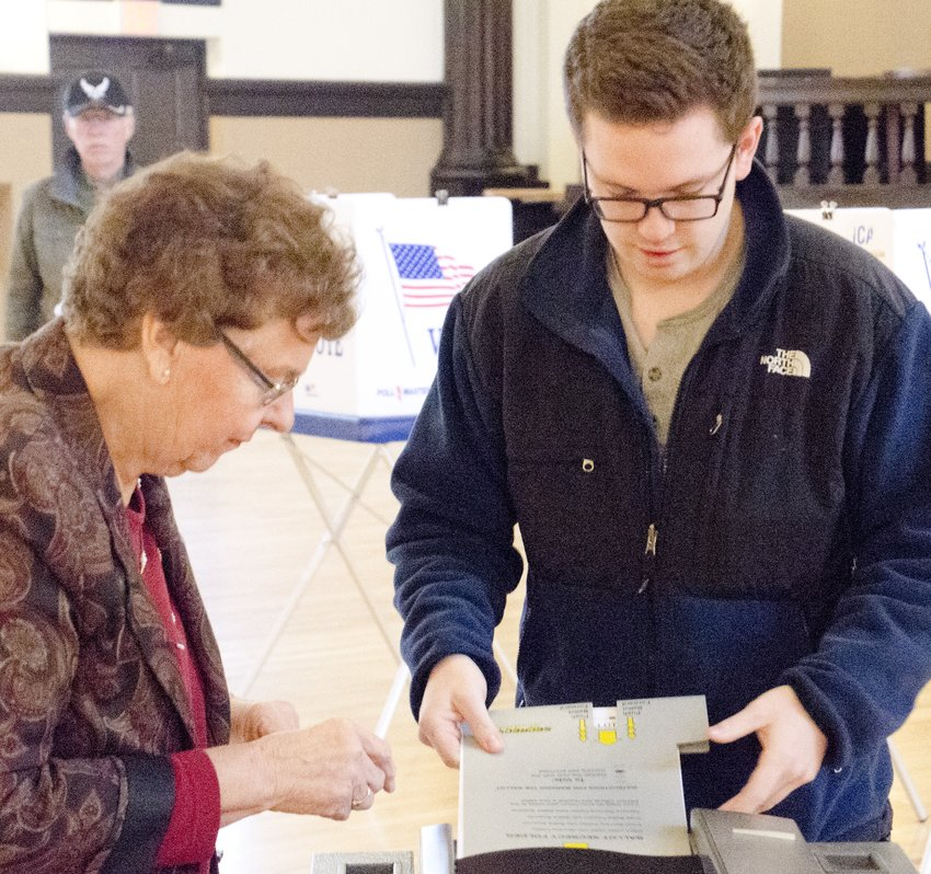 Emmett Claire submits his ballot, while election judge Helen Carroll observes, at Turner Hall on election day, Tuesday, Nov. 6.