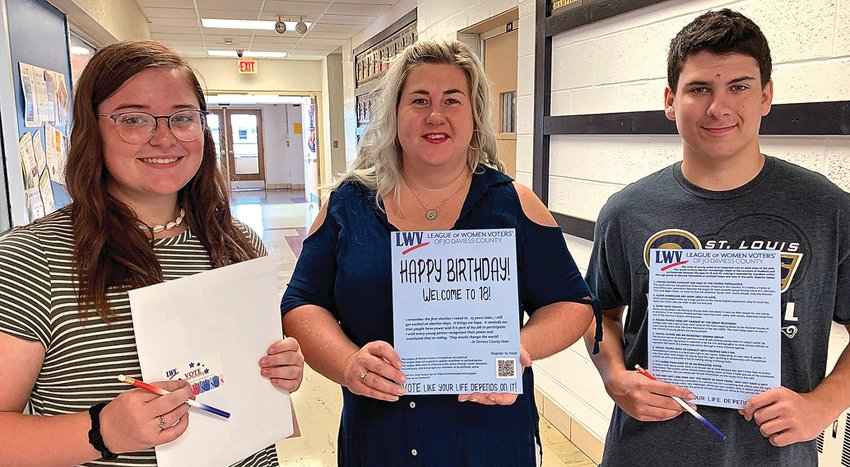 """Galena High School seniors Grace Simmons, left, and Richard Bartell, right, received their """"Welcome to 18"""" voter information packets on National Voter Registration Day, Tuesday, Sept. 24. Kerry Shelke, center, a member of the League of Women Voters of Jo Daviess County, presented the packets at Galena."""