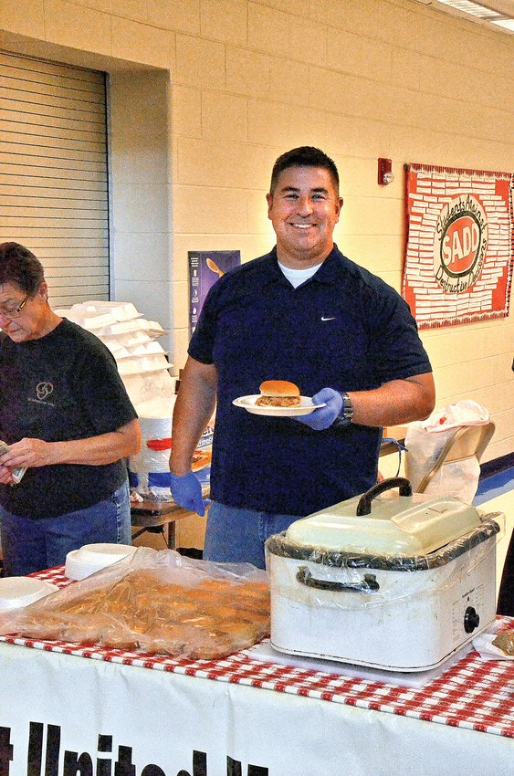 Sheriff Kevin Turner serves turkey and dressing sandwiches during the River Ridge PTO craft fair on Oct. 12. Organizations and River Ridge classes help by serving food and assisting in making the craft fair a success.