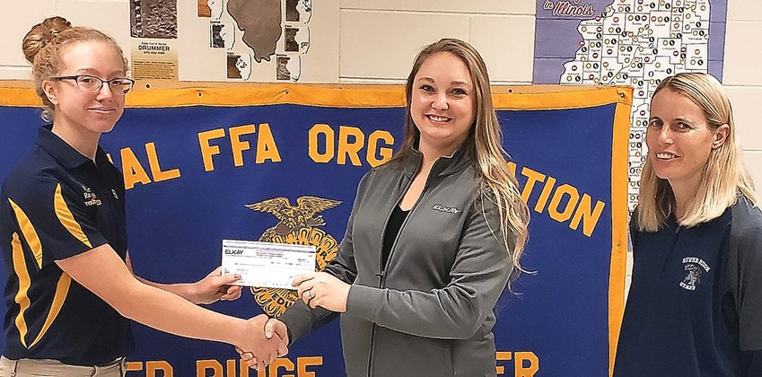 Employees at Elkay came together to help raise funds for the River Ridge FFA Chapter this fall. They bid on company apparel during an in-house silent auction, with all proceeds going to a local organization, chosen by the employees. Sarah Guenzler, Elkay Human Resources, center, presents River Ridge FFA President, Kylie Hiher, left, with the check for $500. Peggy Trone, River Ridge FFA advisor observes.