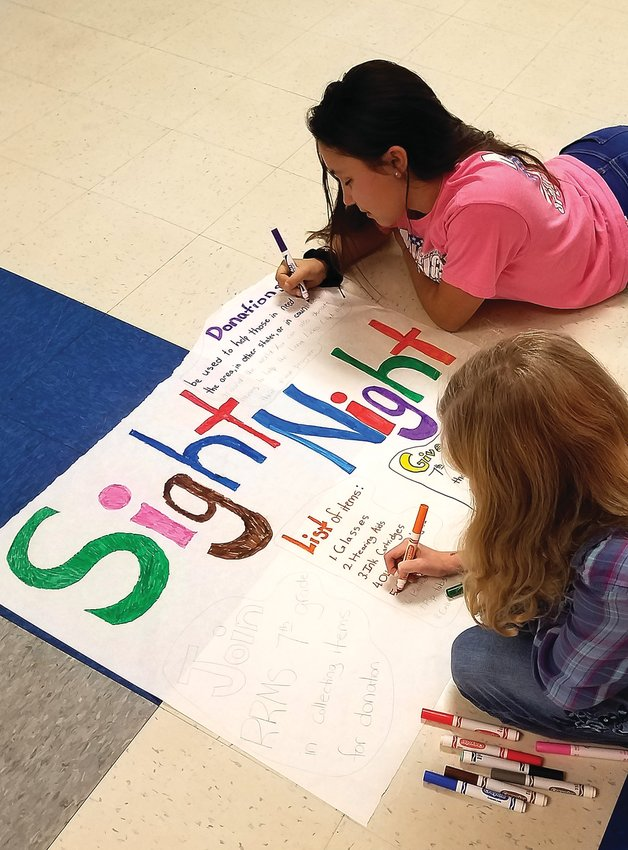 Izzy Haring, top, and Katie Cobine prepare a sign to advertise the collection drive.