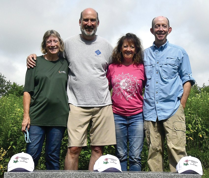 From left: Jay and Brad Rutherford, Darcy Renkens and Bryn Davis pose at the bench honoring their parents, John and Barbara Rutherford. They had special hats made for the grand opening of Rutherford Refuge at Twin Bridges.
