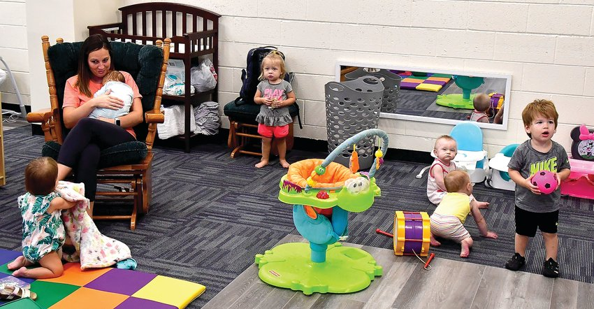 Southwestern daycare's lead teacher Amber Reuter, seated, with Jackson Hilby, talks to Ila Patzner, while Macie Kuhl, Breezy O'Mara, Alijah Reuter and Brecken Slater play in the daycare's infant room.