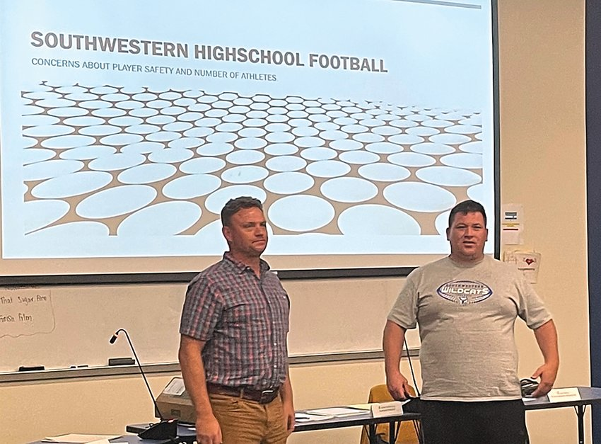 Southwestern assistant football coach Michael Hill, left, and head coach Peter Murphy address a room full of Southwestern players, parents and board members at Southwestern's Wednesday, Sept. 8 board meeting. Brandon Behlke photo