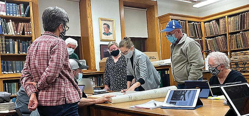 Library board members look over blueprints of a proposed 1991 renovation of the library during the Oct. 11 board meeting. From left: board members Maria Rector, Earl Thompson, John Cox and Tracy Furlong; director Jenna Diedrich; board president Craig Albaugh and board member Katherine Walker.