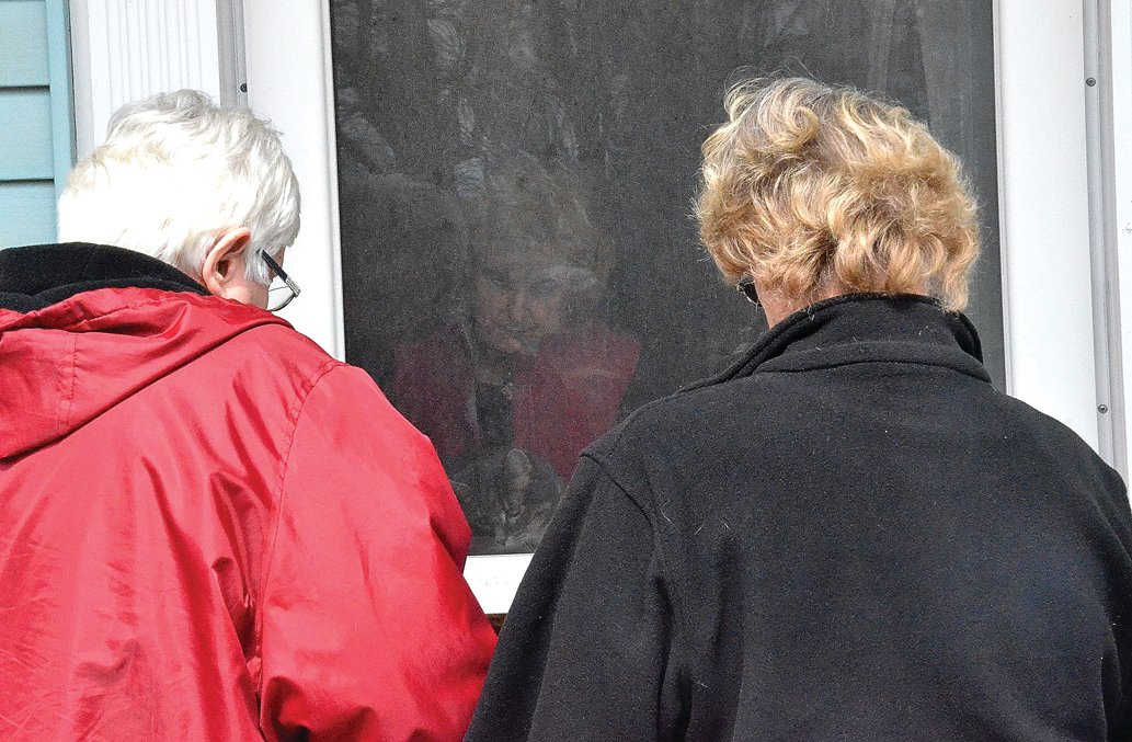Jeanne Ohms and Lorraine Speer stood outside to bless the house, while Patsy Geiger was inside, praying for her family.