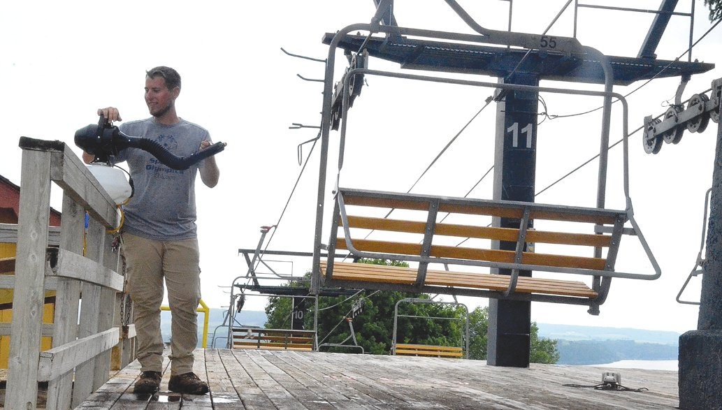 Chestnut Mountain Resort employee Steven Knockel disinfects a chair lift. All employees were required to take a COVID-19 orientation course prior to the opening weekend.