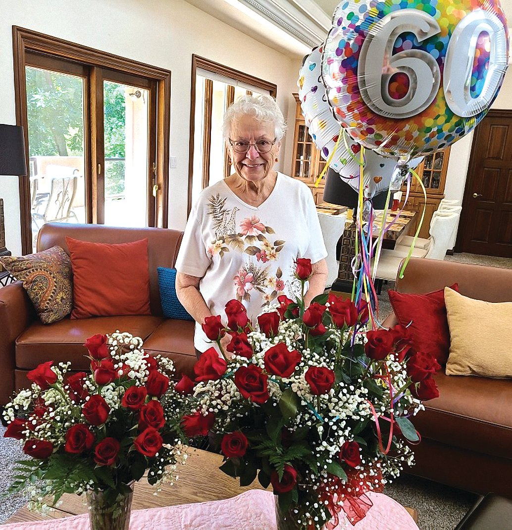 Barbara Blust with the five dozen red roses she received from her husband to celebrate six decades together.
