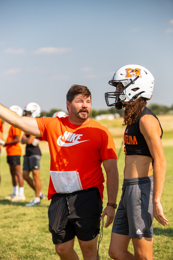 Mangum Head Coach Sam Powers goes over a play with wide-receiver Sawyer Webb Monday.