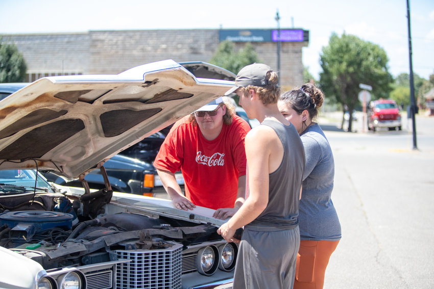 Koby Buchanan, center, shows of his '71 Ford Galaxy 500 at Saturday's car show on the Mangum Square.