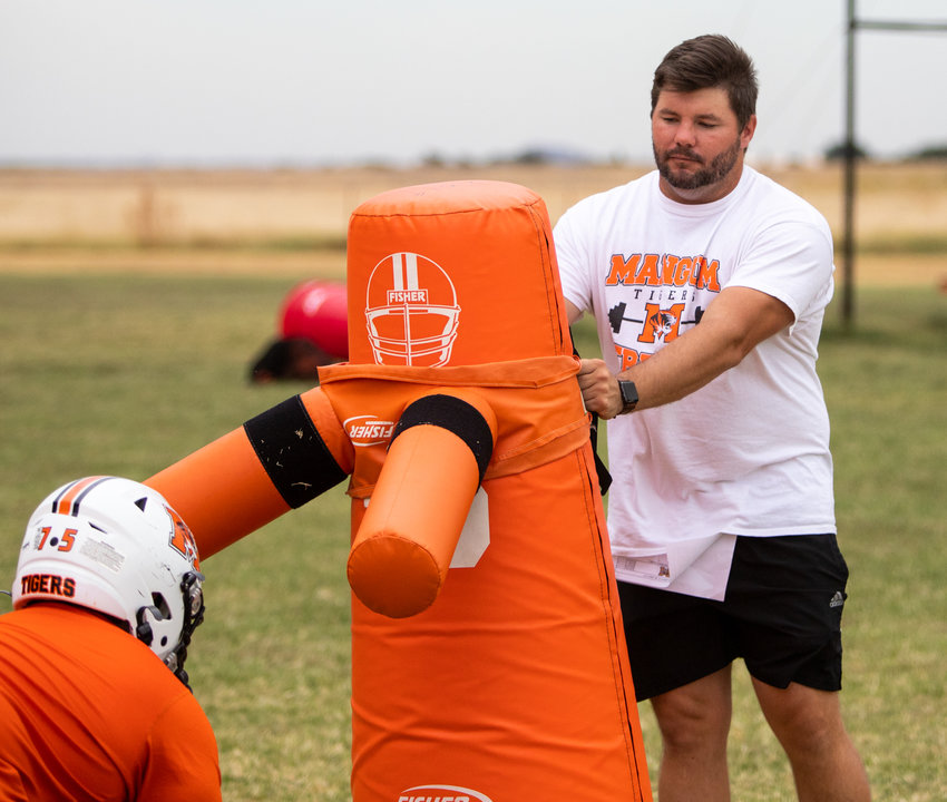 Mangum Head Coach Sam Powers works with lineman during Monday's practice.