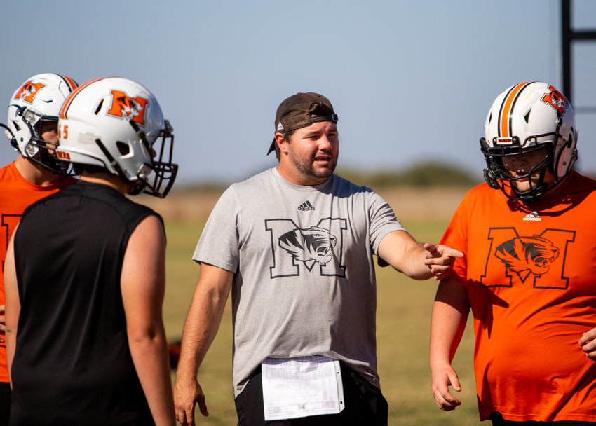 Tigers Head Coach Sam Powers works with his o-line during Monday's practice.