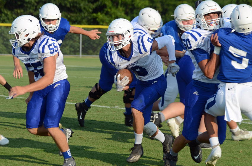 Forrest?s junior standout running back Brenton Burchell (9) follows seniors Brayden Jones (55) and Layne Strasser (60) through a big hole for a nice gain versus Macon County in Tuesday night?s scrimmage at the Murrey E. Holton Memorial Field in Chapel Hill.