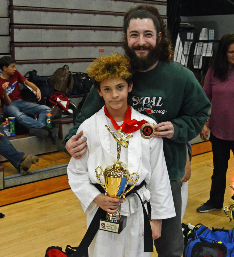 Maddox Puca (left), son of Miles Puca (right) of Chapel Hill and Destin Payne of Columbia, captured the Choong-Sil Taekwondo Federation's 10 and 11 year-old black belt National Sparring Title Saturday at Spring Hill High School.