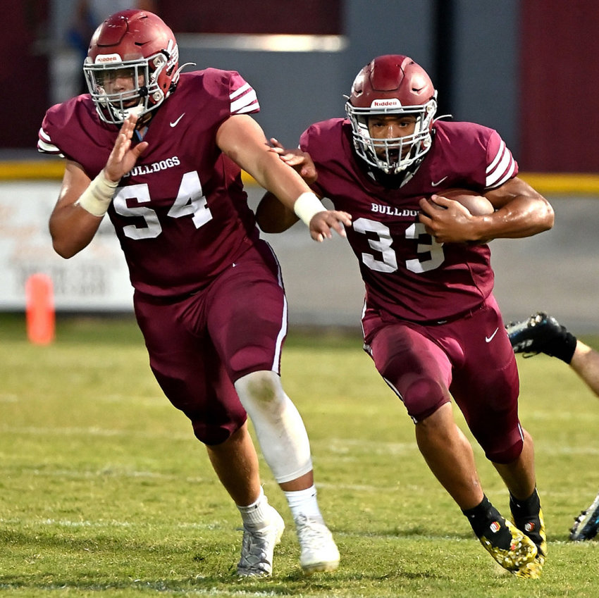 Ben Franklin picks up a block from Barrett Powers (54) and dashes forward for a handful of yards. Franklin finished with 54 yards on 12 touches against Clay County.