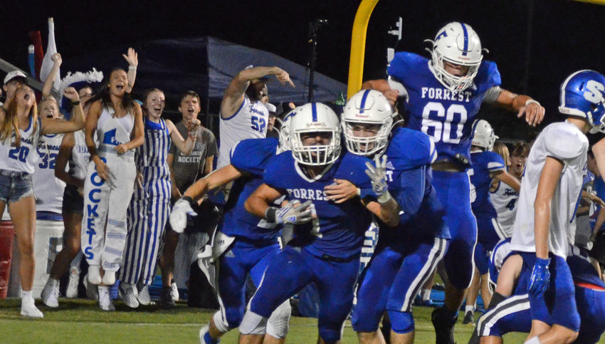 Chris Davis (1) and his Forrest teammates celebrate after Davis scooped up a fumble and scored a touchdown to give the Rockets a 17-7 lead over the Eagles.