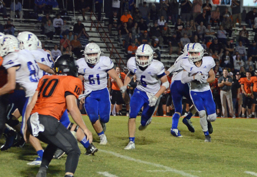 Tayton Swift runs behind Liam Bell (6) and Riley Durbin (61) for a nice gain in the Rockets' big 28-14 win at Richland Friday night.