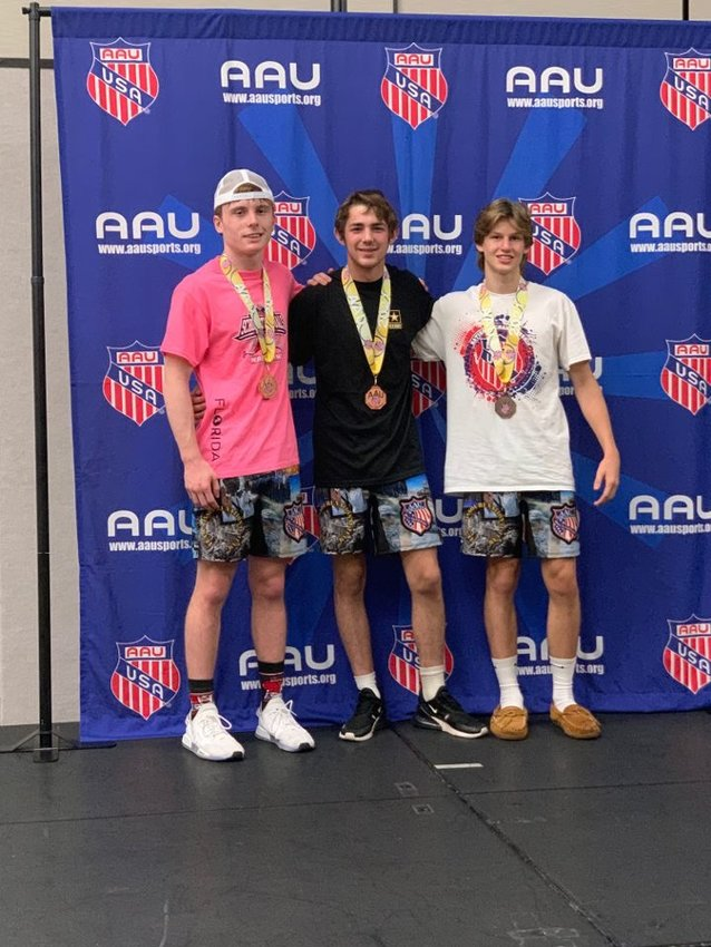 Bulldogs wrestler Dylan Mosley, center, finished third in his weight class at a national AAU tournament last week. Ricky Juarez and Katie Bowen also fared well at the event. [Submitted photo]