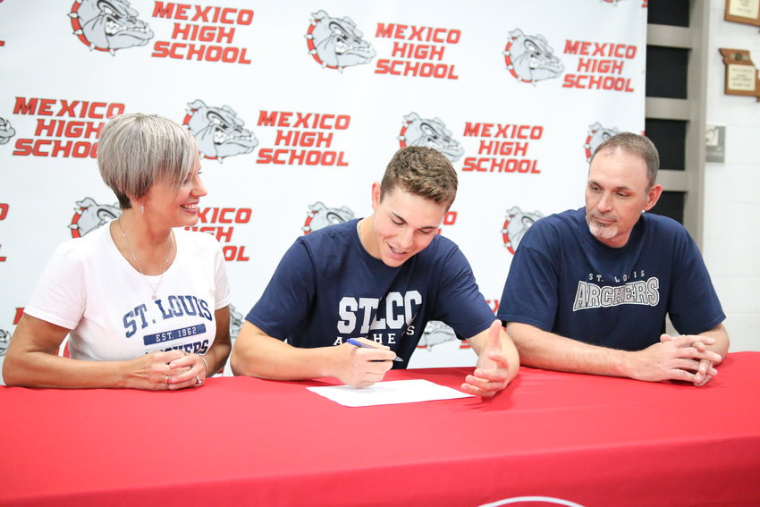 Tonia and Travis Prince watch as Ty Prince signs for the cameras during a ceremony at Mexico High School on Monday. The senior will play baseball at SLCC. [Dave Faries]