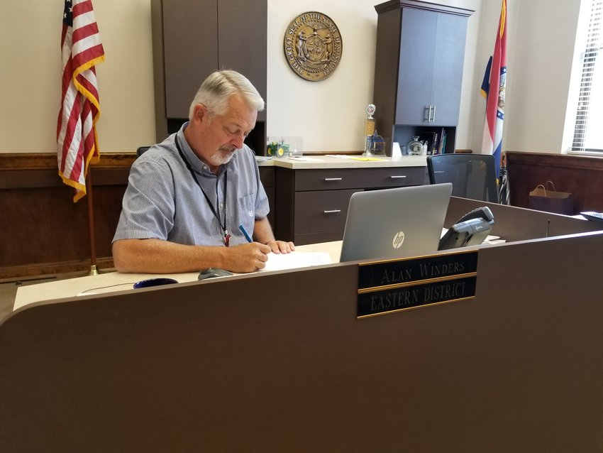 Alan Winders still occupies his old desk in the County Commissioner's office despite being named presiding commissioner. Winders entered government work right out of college. [Dave Faries]