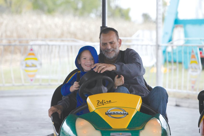 Tommy Meyer, 6, enjoys the bumper cars with grandfather Dan Baker at Play Day Farm on Oct. 15. Both are from New Florence.  Theo Tate photo.
