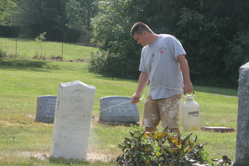 Tanner Smith of Shepherd's Company washes out a tombstone at Bethel Cemetery.