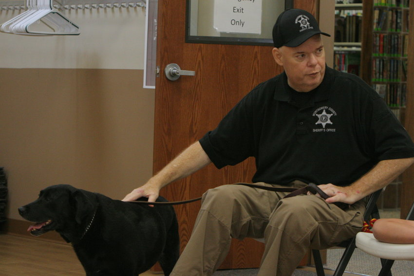 Corporal Clete Mathis talks to the audience about K9 Deputy Lalka during a presentation at the Montgomery City Public Library on July 30.