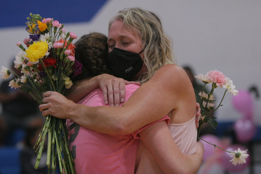 Kelly Flake hugs her daughter, Carson, before the Montgomery County volleyball team's Pink Out match against Centralia on Oct. 5. The Wildcats played the match in honor of Kelly, who was diagnosed with cancer in July. Carson is a junior on the squad.
