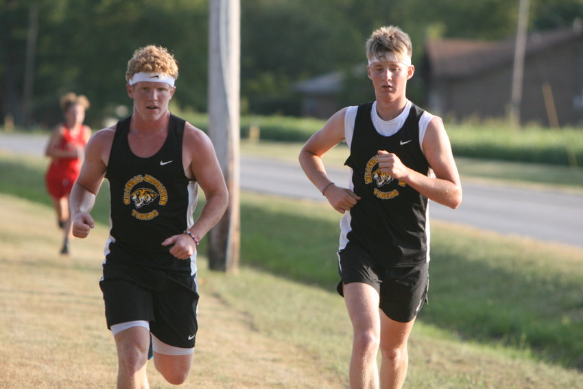 Wellsville-Middletown seniors Keaton Mayes and Isaac Seabaugh compete in the second mile of the Wellsville-Middletown Invitational on Sept. 20.