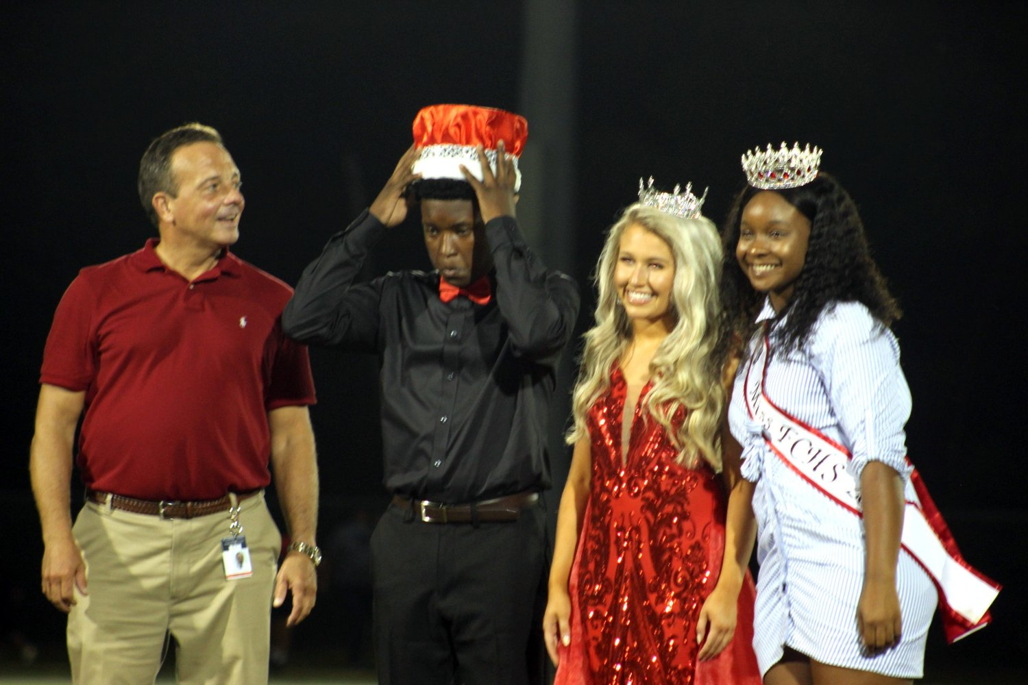 Newly crowned Mr. FCHS, Jarvis Turrell, adjusts his crown alongside the new Ms. FCHS Jadyn Luberto, at halftime of the Sept.  11 pre-season classic. At left is principal Laurence Pender. and at right last year's Ms. FCHS, Honesti Williams