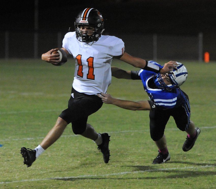 Seth Countess gives a fierce stiff arm and picks up a handful of yards on Friday night at Jackson County.