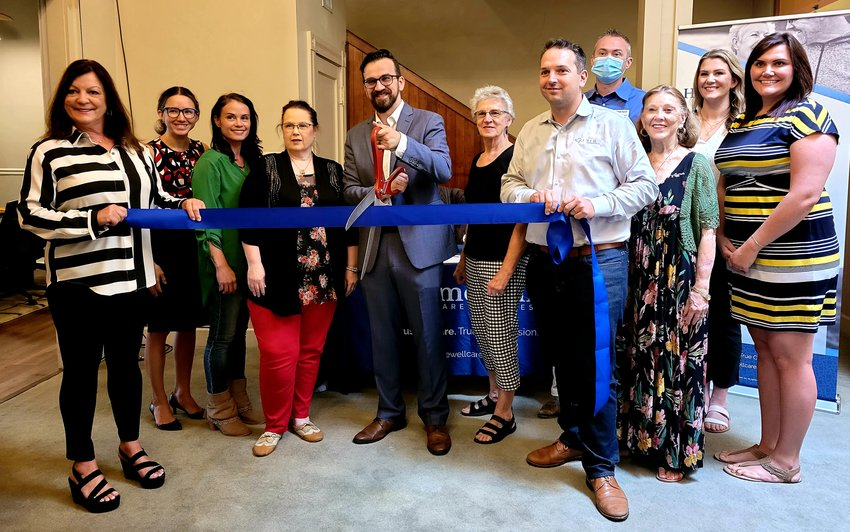 Boris Zecevic, center, opened HomeWell Care Services in March. A ribbon cutting was held on Aug. 19 to commemorate their new office location on the public square.