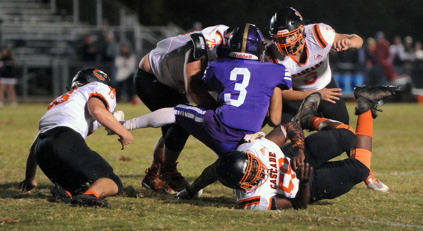 A host of Cascade defenders, including Elijah Arnold (13), Shamari McChristian (58), Ryan Inmon (3) and Austin Powell (75 converge to make the tackle against Community quarterback Dallas Grooms.