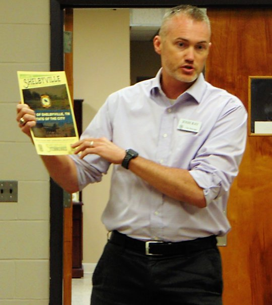 Shelbyville City Manager Joshua Ray holds a flyer explaining the City's new marketing plan for 'whiskey, history, and horses,' which he spoke about at Monday night's Bedford County GOP community forum.