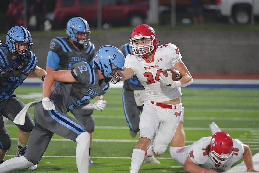 MOVING THE CHAINS — Warrenton running back Joe Goldsmith (34)  gains some yardage in Friday's road game at St. Charles. Goldsmith rushed for a team-best 97 yards on 13 carries in the Warriors' 42-8 victory.