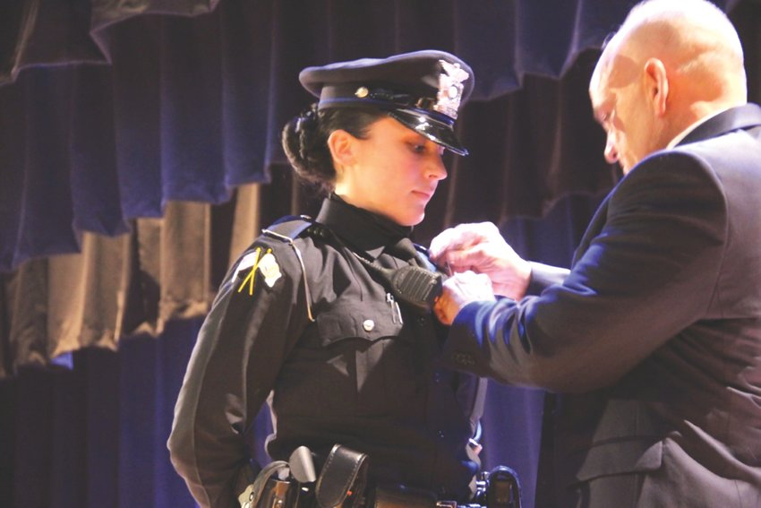 """READY TO SERVE: Officer Keara Enos during the swearing in ceremony on January 21. Enos is """"incredibly thankful to do this job every day,"""" and says she's looking forward to all there is to learn. She is being pinned by her father, Stephen, retired Chief of the Chief in Rehoboth, MA Police Department."""