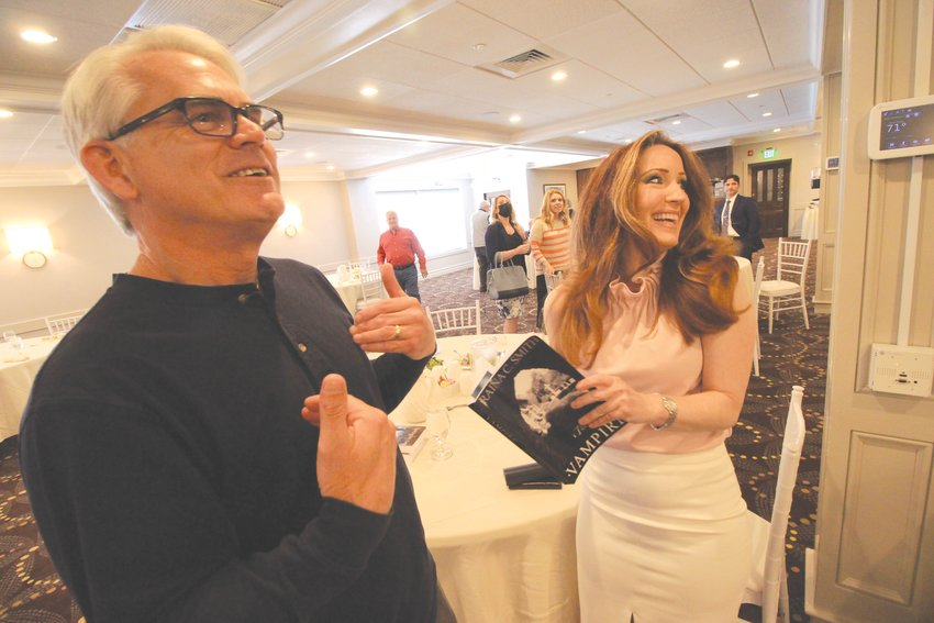 WRITER, AGENT, PUBLISHER: Author Raina Smith and Steve Tilley, a member of the Warwick Rotary Club, exchange stories following her presentation about her books Thursday.