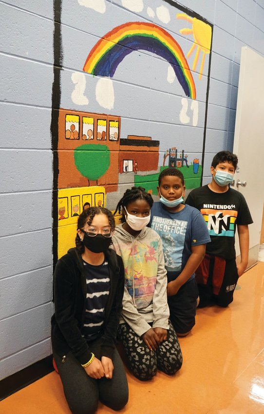 CREATIVE EFFORT: Edgewood Highland fifth-graders Briana Fondeur, Jessica Derisier, Gabriel De Oleo and Juan De La Rosa Bran pose with the mural they've painted highlighting the joy to come post-pandemic.