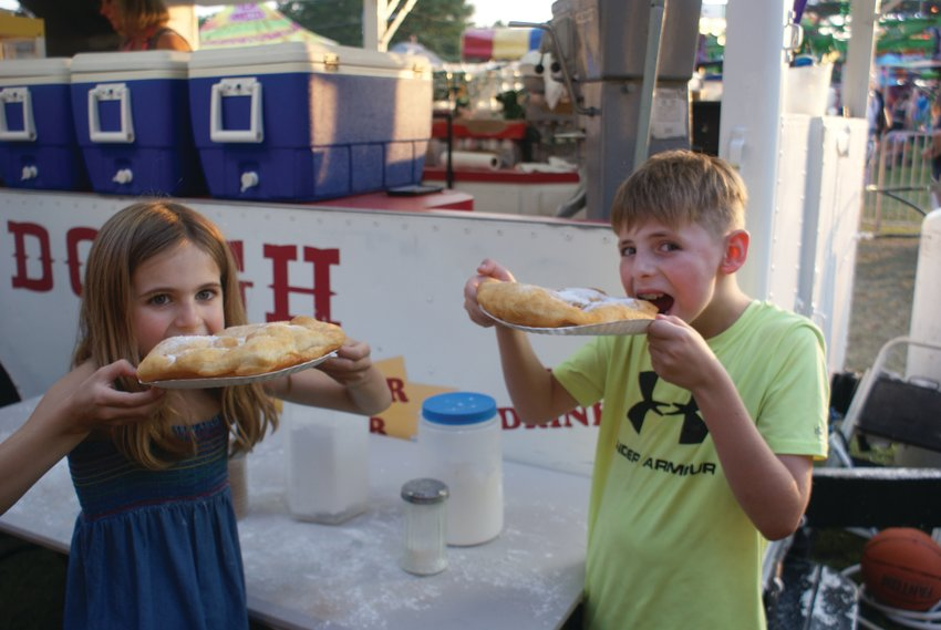 DOUGH KIDS: Enjoying dough boys in the amusement area of the St. Mary's Feast were Macy Casale, 7, and her brother Marco, 10.