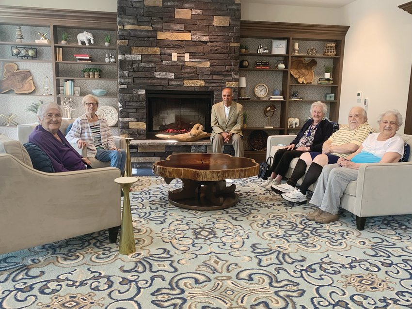 Akshay Talwar, the President and CEO of Briarcliffe, (center) has gathered with Preserve residents in the residence's welcoming lobby which is anchored by this live-edge puka wood table ~ given to Akshay as a special gift by his father.