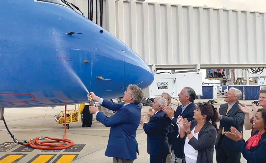 CELEBRATING WITH A SPLASH: State leaders and RIAC members gather on the tarmac as Trey Urbahn, Breeze Airways co-founder, gives the plane a champagne christening.