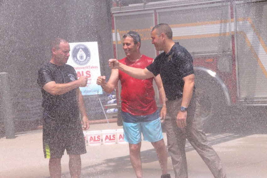 NOT WET ENOUGH: Mayor Picozzi, Fire Chief McMichael, and Police Chief Connor decided the rainy summer hadn't soaked the state enough, and got drenched on Tuesday for ALS research. Here they bump fists under a shower provided from a ladder truck in front of Station 1 in Apponaug Tuesday.