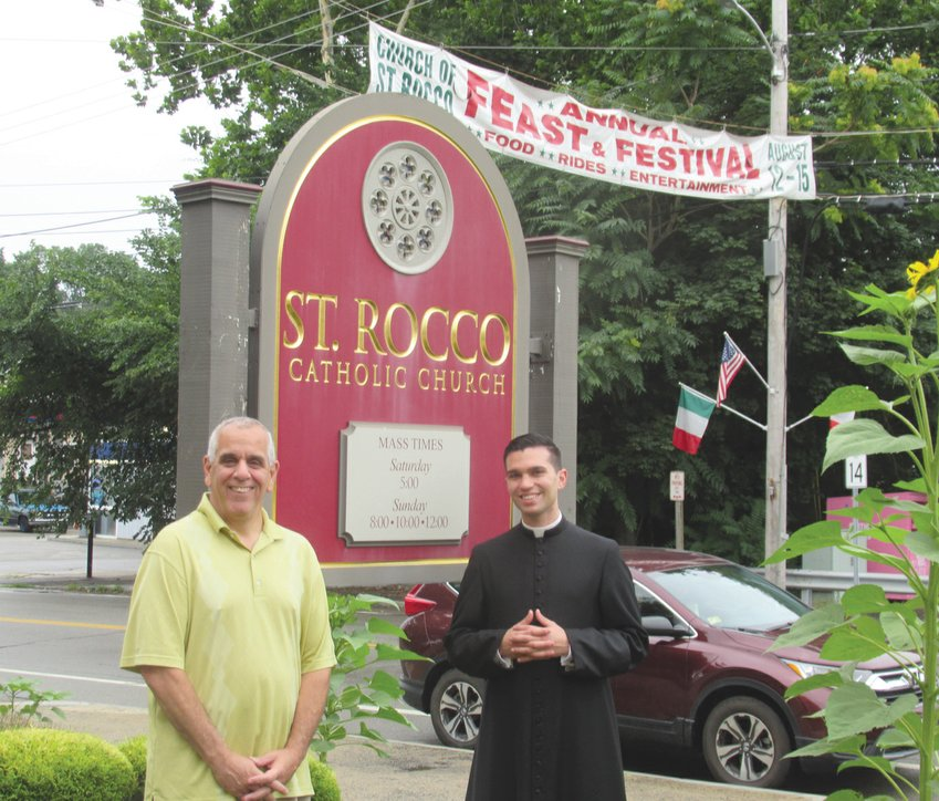 DIVINE DUTY: Richard Montella, left, long-serving co-chairman of the now 81-year-old Saint Rocco's Feast and Festival, is joined by Seminarian Stephan Coutcher outside the Roman Catholic Church conveniently located on the corner of Plainfield Pike and Atwood Avenue in Johnston. (Sun Rise photos by Pete Fontaine) PIX TWO IMG 4178
