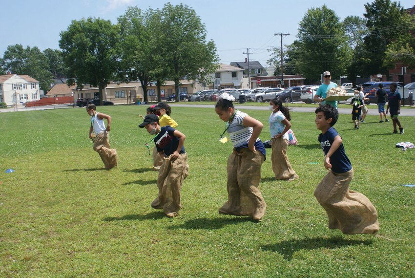 A HOP AWAY: Students celebrated the completion of Camp XL at Bain Middle School, enjoying activities such as sack races.