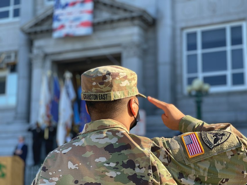 PAYING TRIBUTE:A Cranston East JROTC cadet salutes during the playing of the national anthem at Saturday's 9/11 observance.