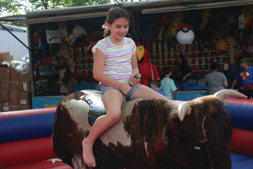 HOLD ON TIGHT: Zayleigh Falkowski, 10, rode the bull at this past weekend's Gaspee Day Arts & Crafts Festival. She was able to complete the entire ride.