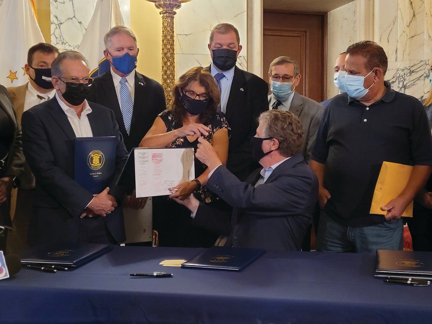 """RYAN'S BILL: Rhode Island Gov. Dan McKee handed the pen he used to sign the legislation that may ultimately be known as """"Ryan's Law"""" to co-sponsor state Rep. Deborah Fellela, who then gave the pen to Cranston resident and Johnston native Lou Massemini, who's son's death helped inspire the bill."""