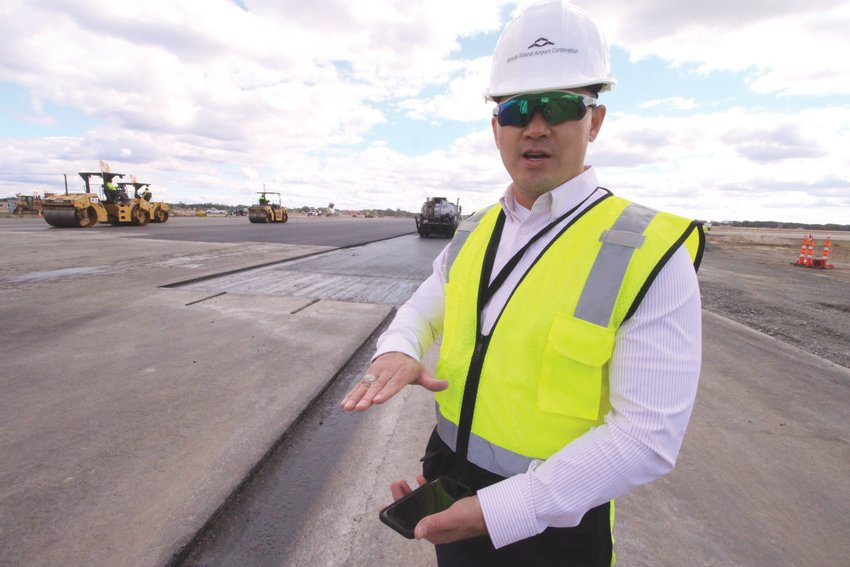 IT'S THAT THICK: Duc Nguyen, chief infrastructure officer at the Rhode Island Airport Corporation, beside a section of Runway 16-34 set to receive another layer of asphalt.